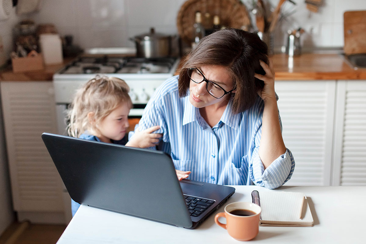 Mother simultaneously working on laptop and caring for daughter
